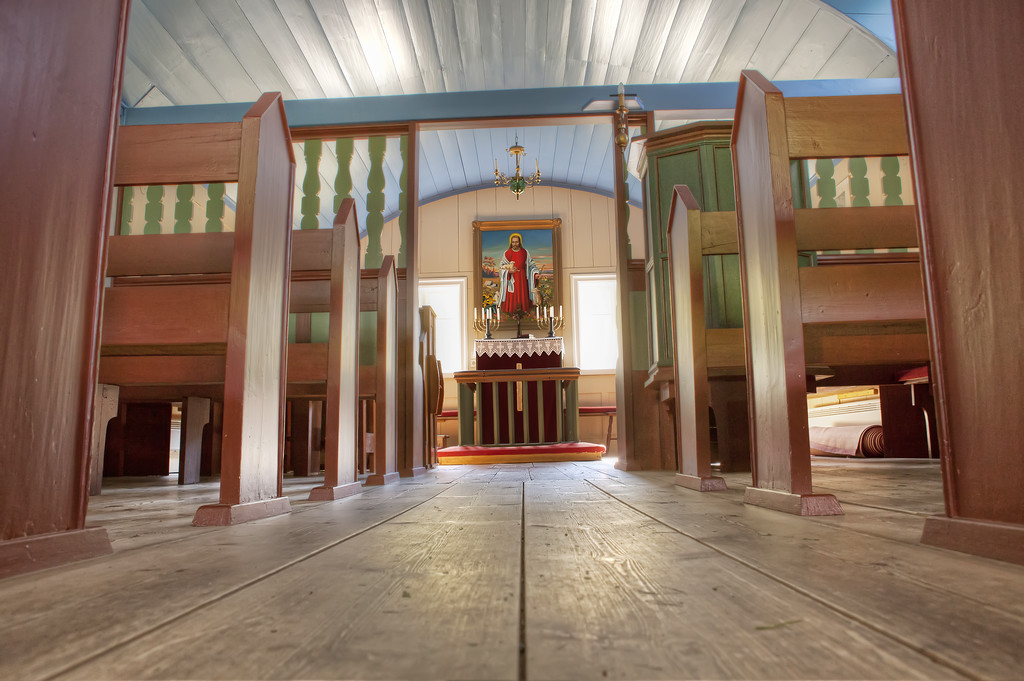 interior of Icelandic turf church with view from pews with altar and painting of jesus