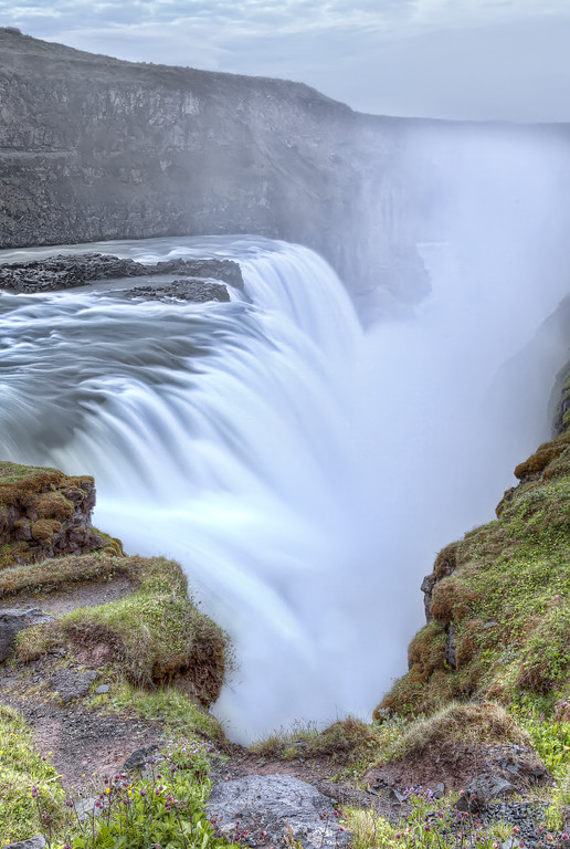On the edge of Gullfoss waterfall in Iceland where the water tumbles down into a giant chasm.