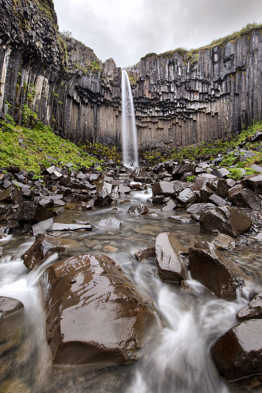 Waterfall in Skaftafel National Park, Iceland with a thin delicate stream of water that spreads out as it plunges into a deep pool surrounded by harsh decaying hexagonal columns of granite.