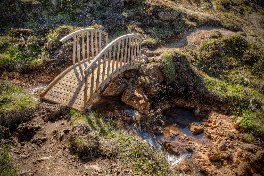 Wooden bridge along path over rocky stream to Godafoss, Iceland