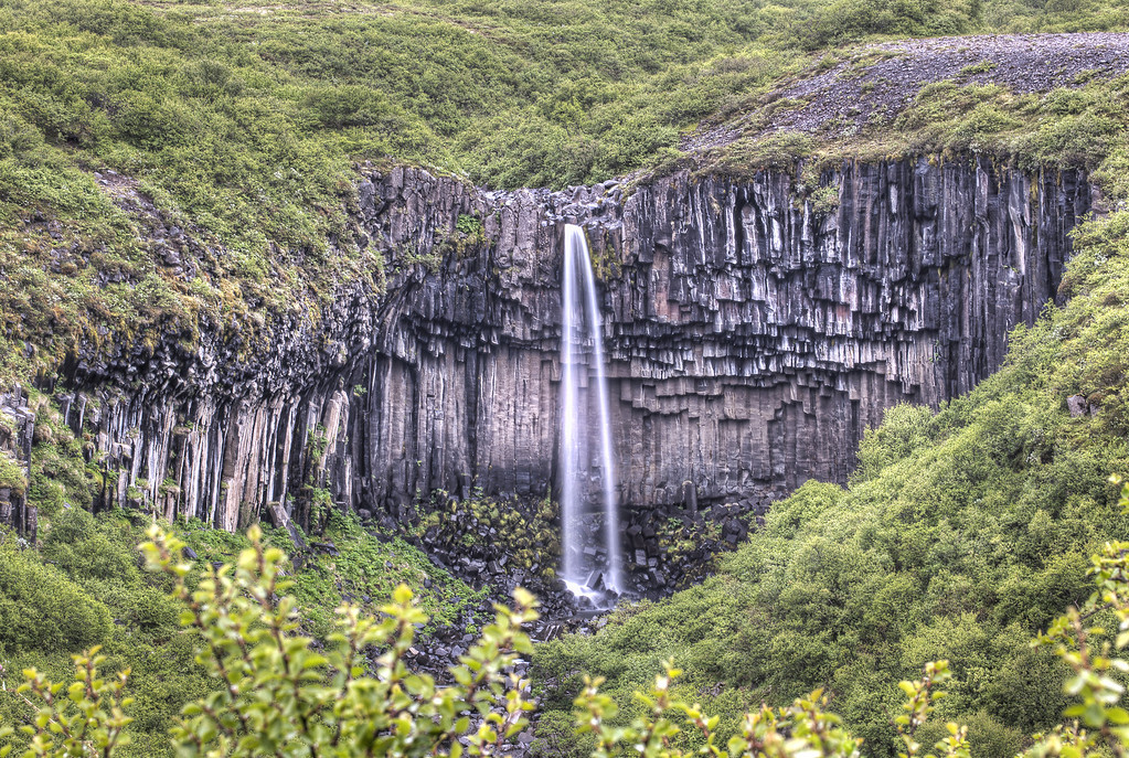 Photo of a waterfall, Svartifoss, in Iceland. A smooth surtain of water fans out in front of hexagonal columns of black basalt