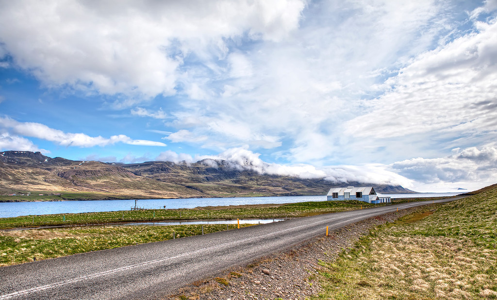 An empty road with a lone building on the shoreline while clouds poured off of the mountains into the entrance of the fjord in East Fjords, Iceland.