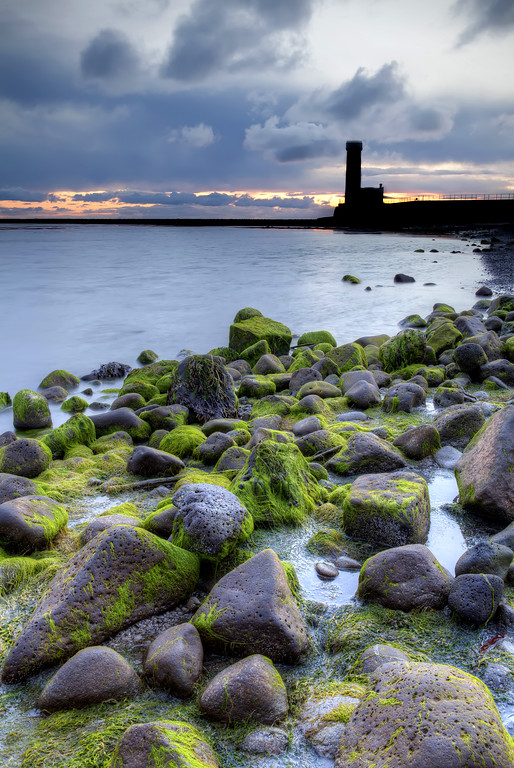 Shoreline with rocks covered in green moss with calm water and lighthouse in the distance with pink light showing under the cloudy sky in Gardur, Iceland