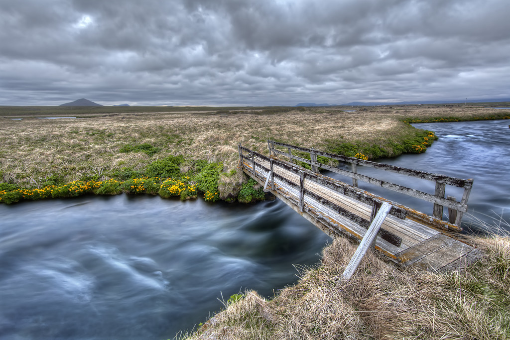 An old, dilapidated, rickety, bridge spans a small river surrounded by barren landscape in Iceland.