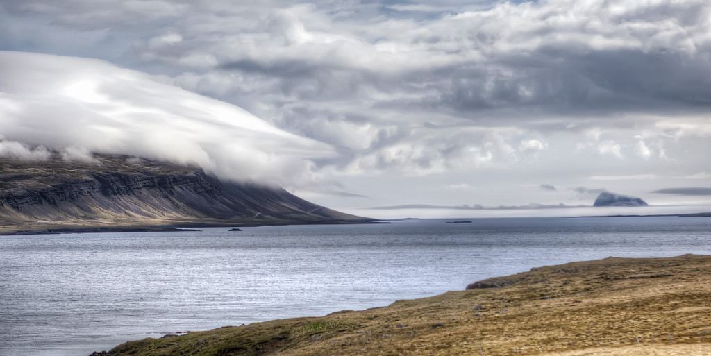 Coastline of Eastfjords, Iceland where cloud mass moves down the mountain over the ocean.