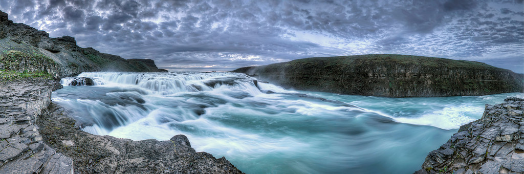 Panoramic view taken above the main falls of Gullfoss in Iceland, looking up stream at a smaller fall just before the river careens into a gaping chasm.