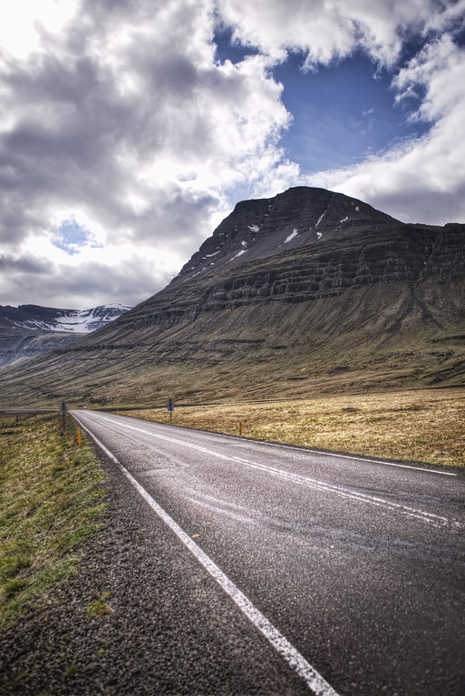 Long straight road through Iceland's East-fjords with rugged mountain.