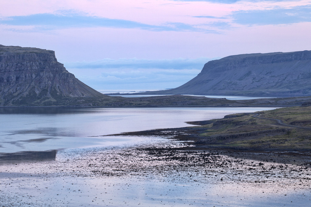 View of huge cliffs peacefully in the distance of the fjords with a soft pink light overhead reflecting on the water in Westfjords, Iceland.