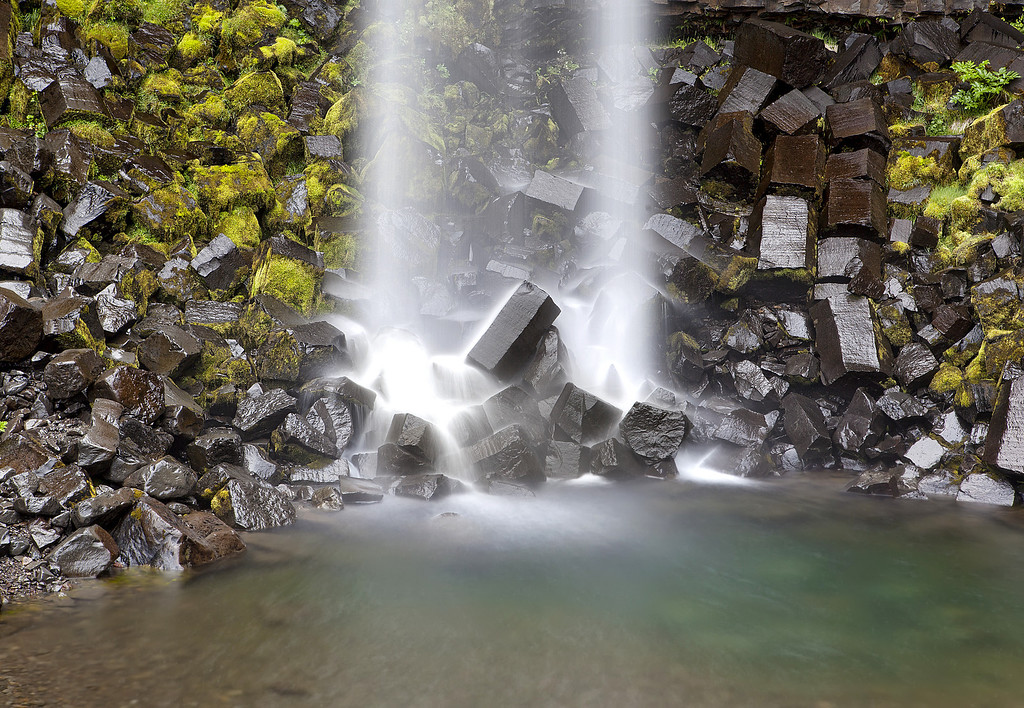 Thin veil of water tumbling on to the jagged rocks covered in green moss landing in a pool of water at the base of Svartifoss waterfall in Skaftafel, Iceland