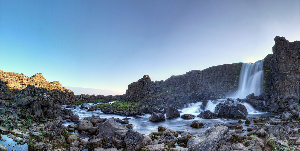 Panorama of waterfall falling from cliff side flowing over moss covered rocks in stream with bluish purple sky above at the Rift, Iceland