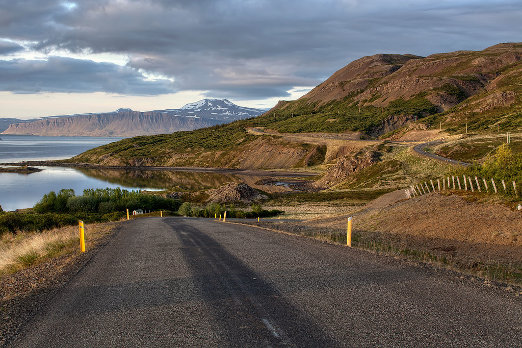 Road along the coast in Westfjords, Iceland with 3 bends that peeked in and out with the sun was just rising over the mountains behind.