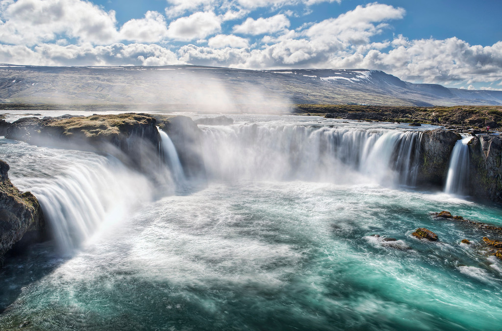Panoramic view of powerful Godafoss waterfall powering over cliffs and entering the turquoise waters of Skjalfandafljot River in Iceland.