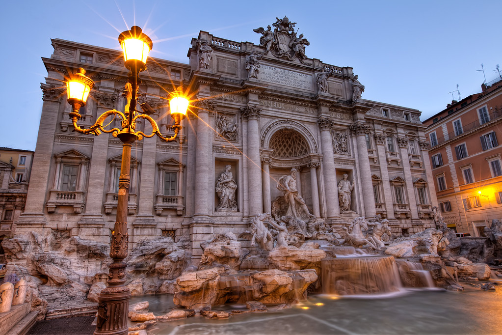 The Trevi Fountain in Rome before sunrise with glowing street lamp in foreground - very detailed high resolution photo.