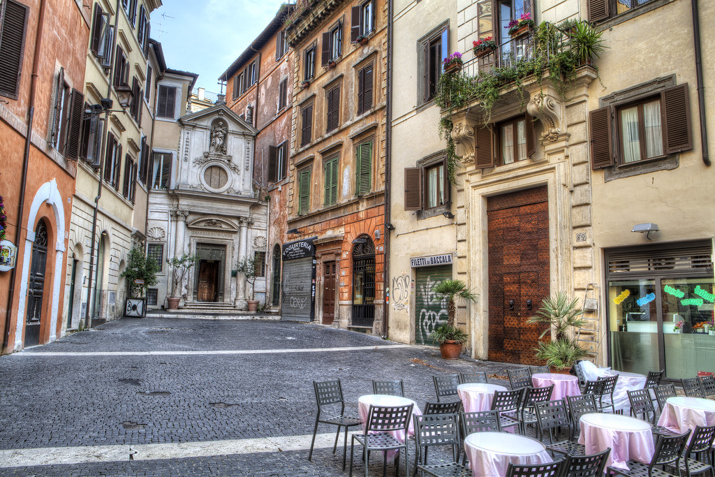 Small square in rome with tables and surrounded by buildings