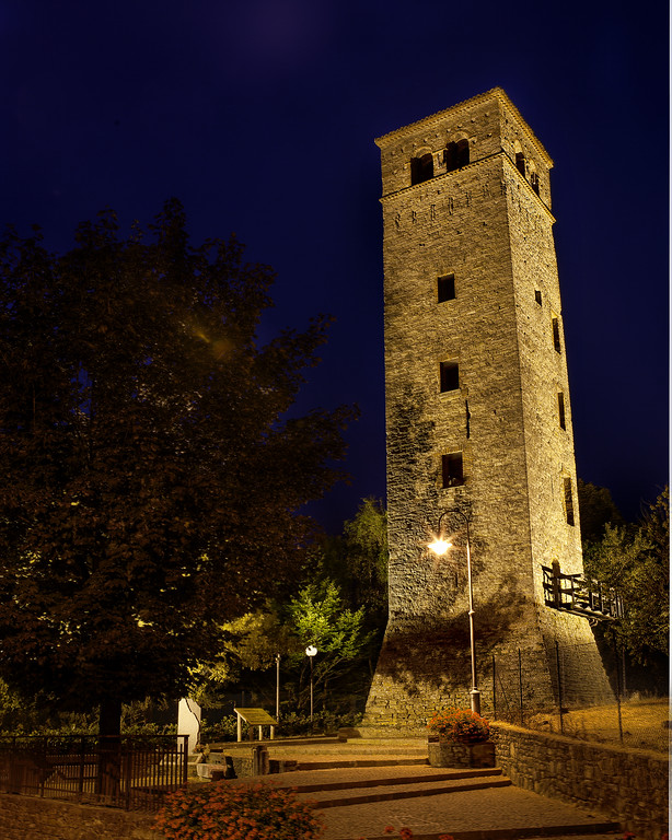 Medieval stone tower with golden light and purple night sky in Acqui Terme, Piedmont, Italy.