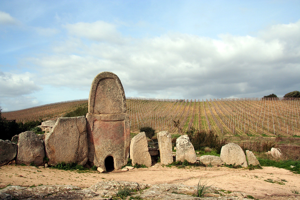 giants tomb in sardinia facade of monolith in front of barren vineyard
