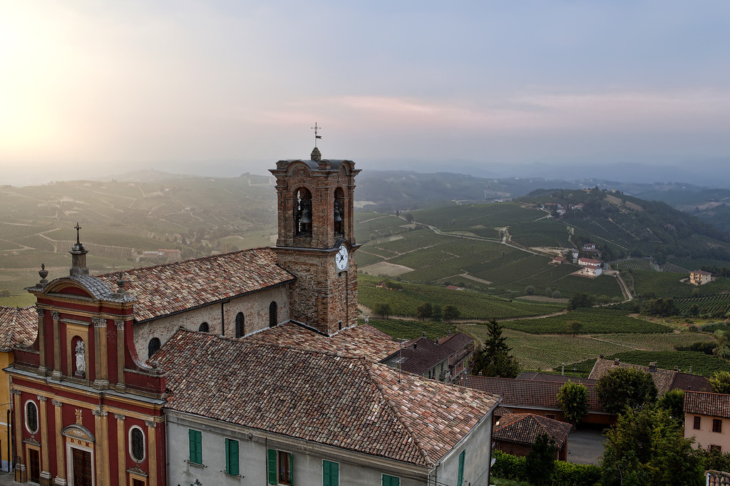 Church in Alice Bel Colle, Italy showing colorful red and yellow facade with bell tower set over rolling countryside.