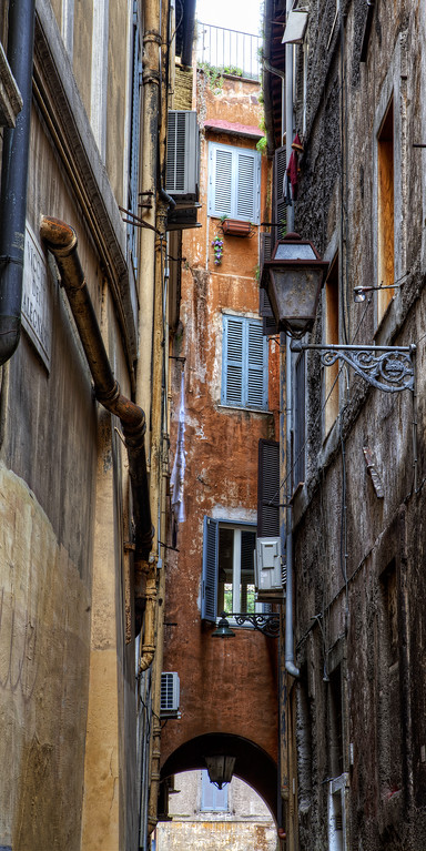 a pretty alleyway in rome with archway and peeling orange paint
