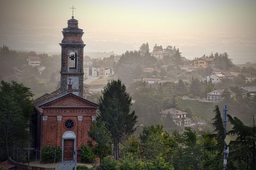 Church on hill with bell tower overlooking the countryside on a hazy morning in Alice Bel Colle, Piedmont, Italy.