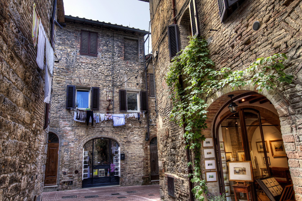 A leafy alleyway  with laundry hanging out to dry in San Gimignano, Italy.