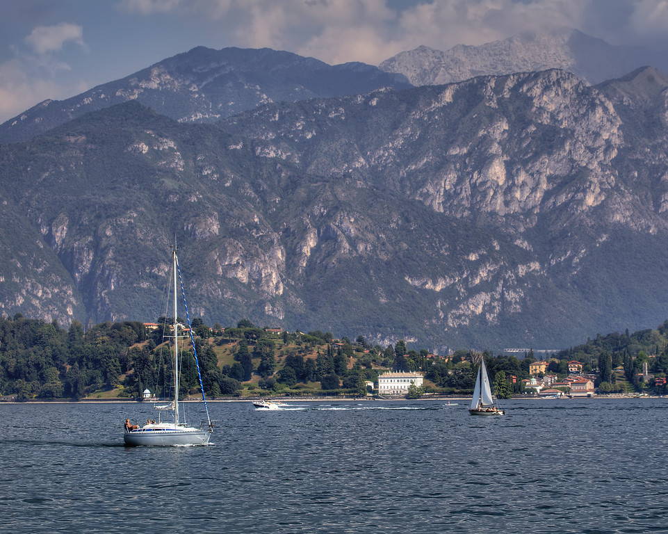 Sailboats on Lake Como in Italy with mountains rising from the deep water to the blue sky.