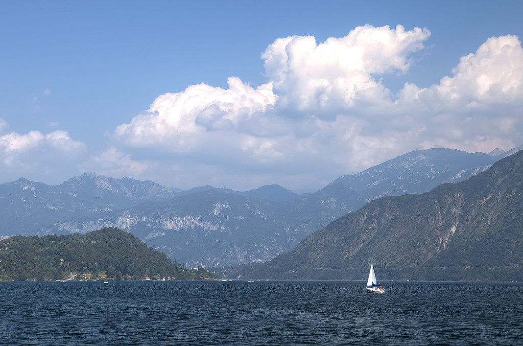 Sailboat dwarfed by the surrounding mountains that rise, almost vertically, from the water's surface on Lake Como, Italy.