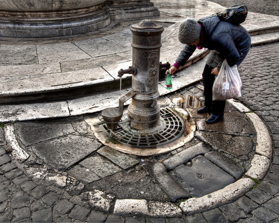 woman using water fountain in rome to fill her bottle near the pantheon