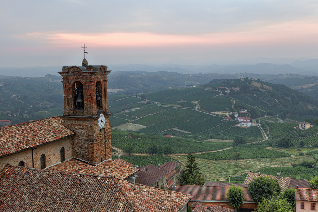 View of landscape from Alice Bel Colle, Piedmont, Italy from church with bell tower and tile roof showing rolling hills and vineyards with pink sky peeking through clouds at sunrise.