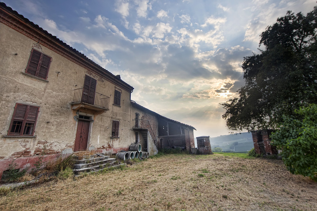 Rundown old stone villa among the vineyards with trees framing the remnants of sunrise in Piedmont, Italy.