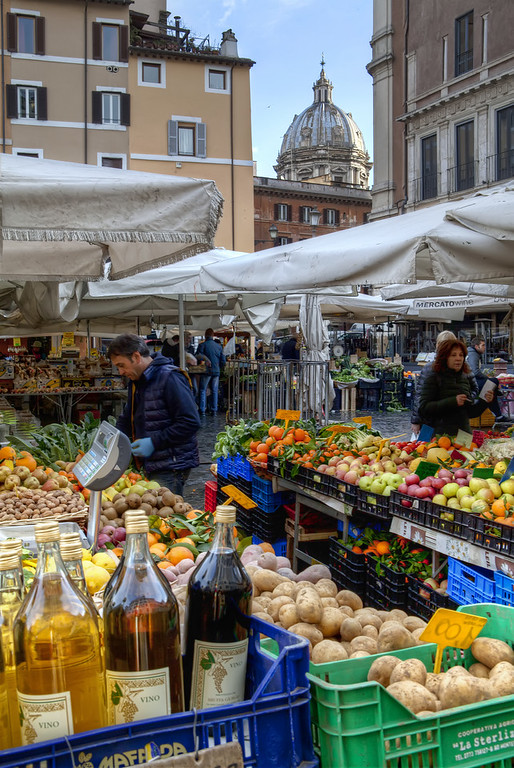 market in rome with wine fruits and vegetables and a dome in the background