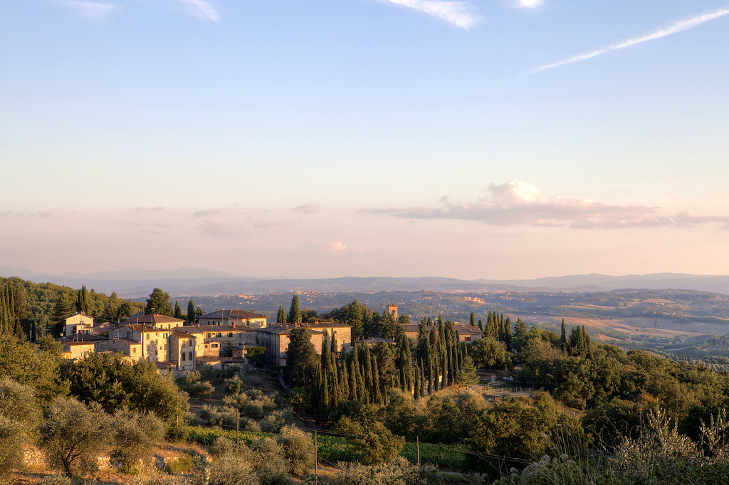 A photo of a small village on a hilltop in Tuscany as dusk falls