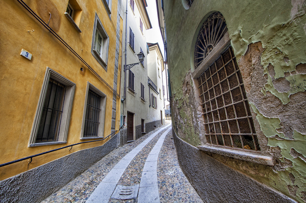 Narrow alleyway with yellow building on left and on right building with green peeling paint surrounding an interesting window in Acqui Terme, Piedmont, Italy