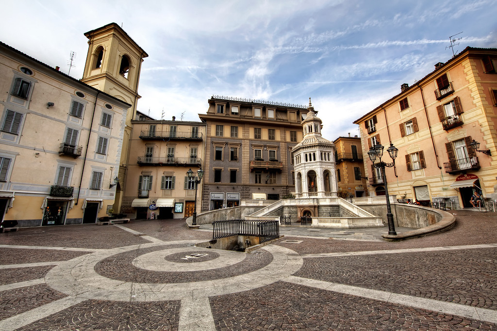 Piazza Bollente with it's sulfuric scented 75° Centigrade fountain with light and dark cobblestone designs surrounded by attractive stone buildings with shops and restaurants in Acqui Terme, Piedmont, Italy