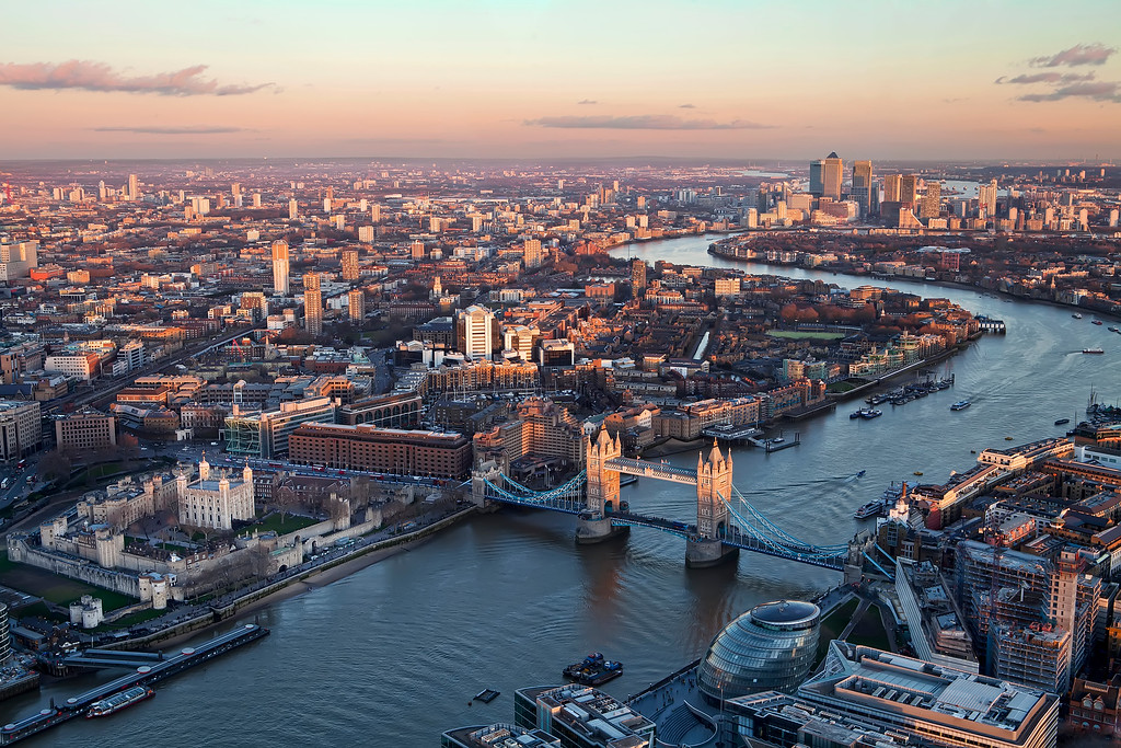 View of London from above in the Shard including the tower of london, tower bridge, city hall, and canary wharf as well with the Thames weaving up from the bottom left corner to the top right