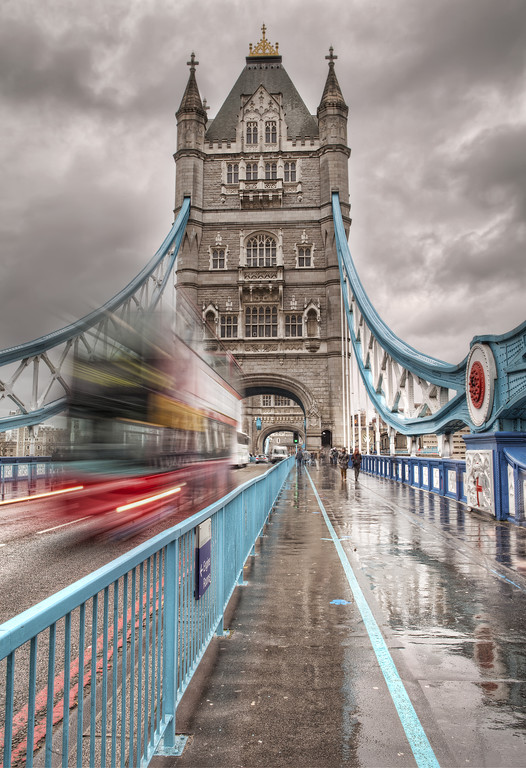 One of the towers of tower bridge, London, taken from on the bridge, with a blurred double decker bus on the road in front.