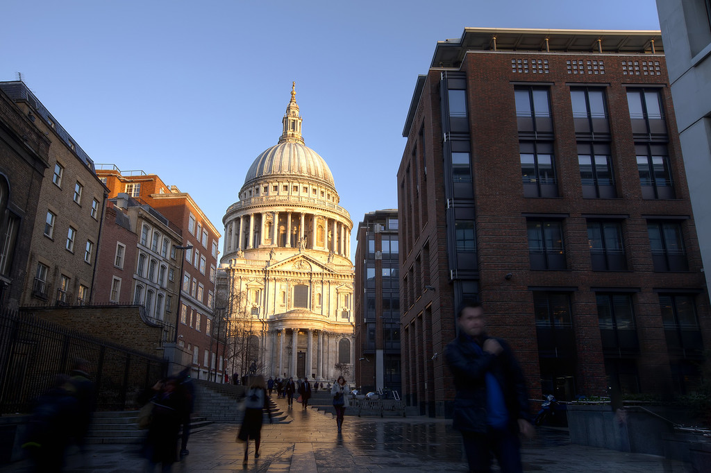 approaching the dome of st. pauls cathedral blue sky blurry moving people and surrounding buildings