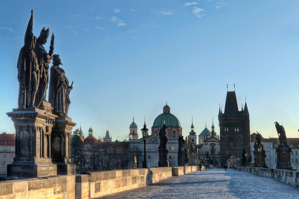 Charles Bridge in Prague overlooking the old town under blue sky and golden light.