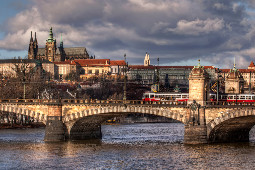 View of Prague showing the contrast of the old buildings, including the Prague Castle and the St. Vitus Cathedral, and the bridge with the modern addition of the tram.