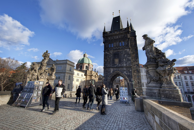 Charles Bridge in Prague looking lively with people and vendors on a beautiful blue sky day.