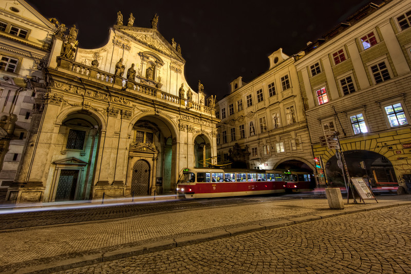 Ornate building in Prague with cable car speeding out of a tunnel in front.