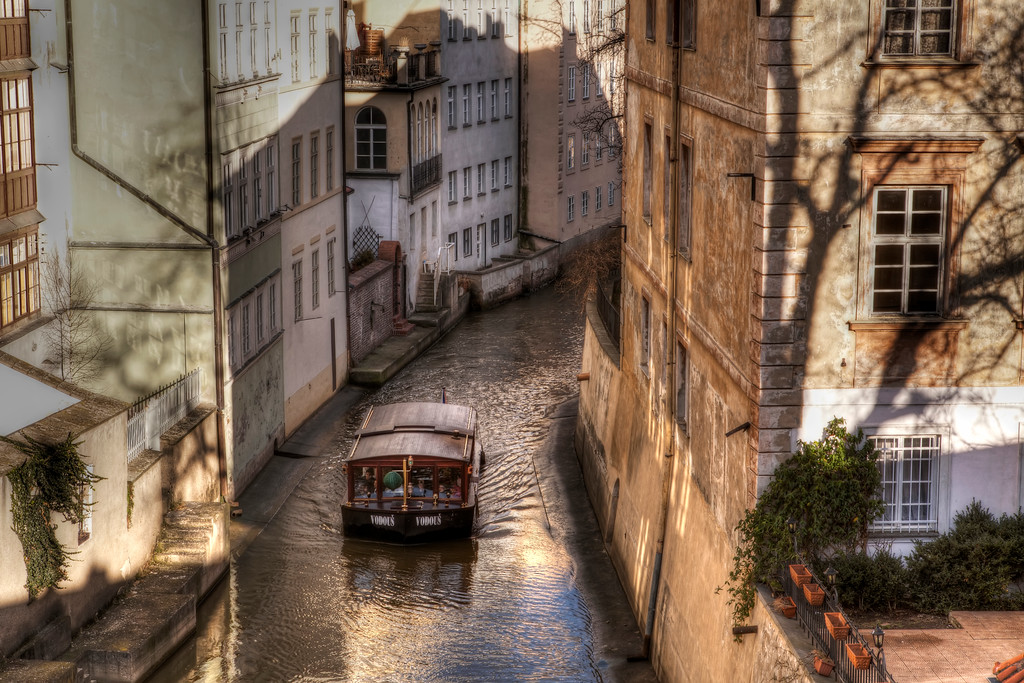 Boat sailing in canal that runs underneath the Charles Bridge, Prague with shadow of buildings on opposite wall.