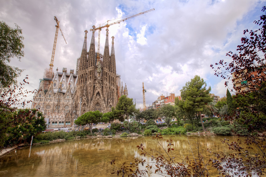 la sagrada familia, Barcelona from the park with pond and cranes still under construction no tourists no people blocking view