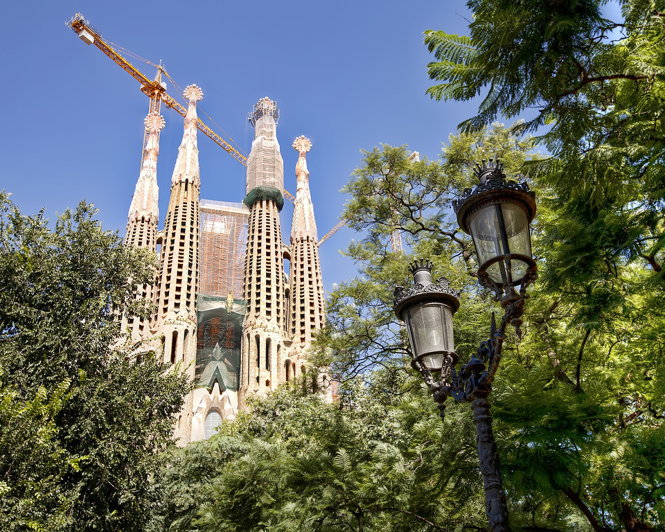 La sagrada famiia in Barcelona framed by trees and a lamppost with a blue sky in the background