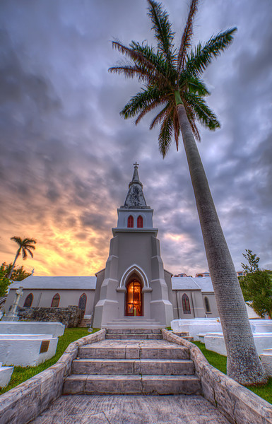 Trinity Church in Bermuda at sunrise with golden glow from inside and royal palm and steps in front.
