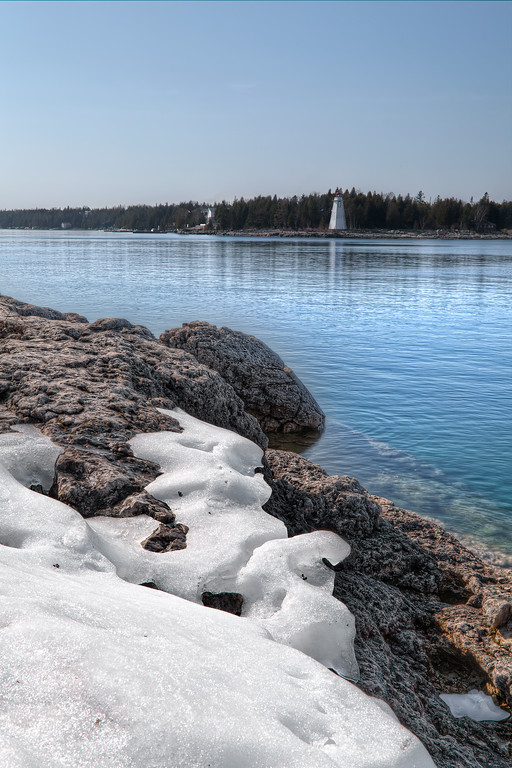 Spring thaw at Lake Huron in Tobermory with snow melting on rocks at lake edge and Big Tub lighthouse across the water