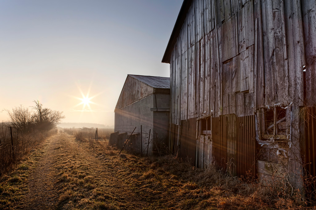 Dilapidated wood and corrugated metal barn on a dirt road with a bright sunburst sky in Ontario, Canada.
