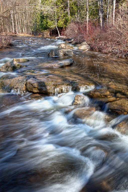 Water flowing fast over rocks in spring with early spring foliage in Bruce County, Ontario, Canada