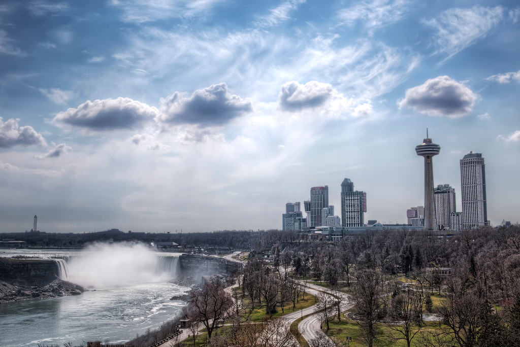 View of Niagara Falls with the buildings of Niagara including the replica CN Tower under a blue sky with five fluffy clouds.