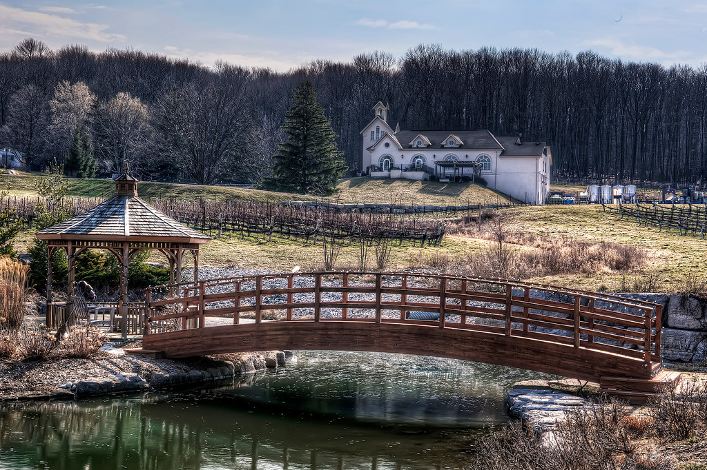 Winter vineyard with white house, wooden bridge and gazebo in Niagara, Ontario.