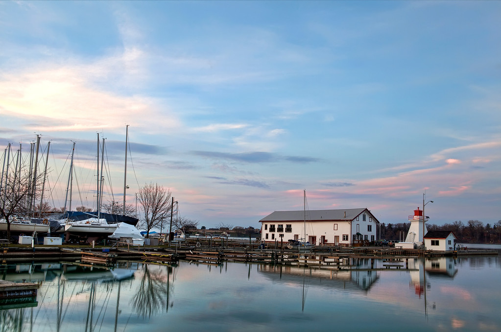 Beautiful sunset on the shores of Lake Ontario, Niagara-on-the-Lake with a boat house and sail boats are on the dock with the lake reflecting the sky.
